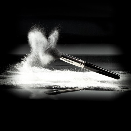 brush in: an image of a cosmetic powder brush, thrown in white loose powder, shot on black backgrownd. Stock Photo