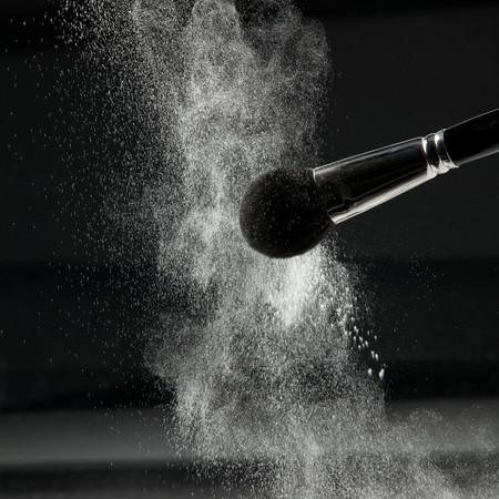 a detail of a powder brush, shaking off white loose powder, shot on black backgrownd. Stock Photo - 8259291