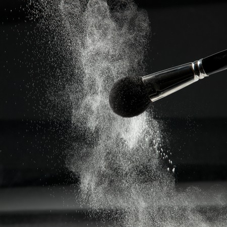 loose skin: a detail of a powder brush, shaking off white loose powder, shot on black backgrownd. Stock Photo