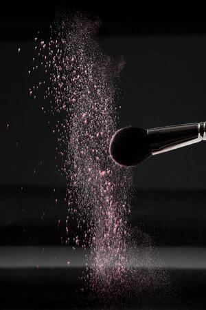 blush: a detail of a blush brush, shaking off white loose powder blush, shot on black backgrownd.