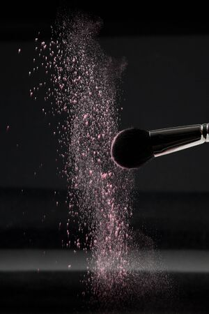 artistas: un detalle de un pincel de rubor, agitando fuera blanco polvo suelto de rubor, filmada en backgrownd negro.
