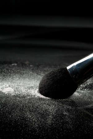 a detail of a powder blush, picking up white loose powder, shot on a black backgrownd photo