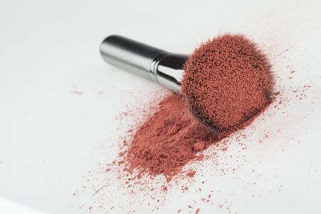 a flat blush brush with pink blush on it, placed on some loose powder blush, shot on white backgrownd. photo