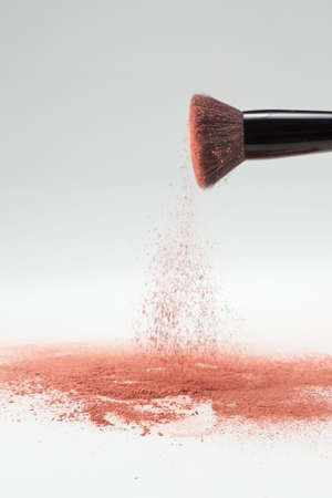 a lateral view of a flat blush brush, shaking off pink loose powder blush, shot on a white backgrownd. photo