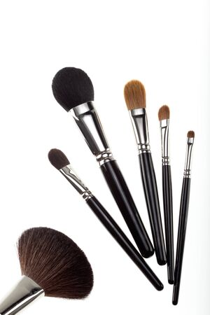 counterbalanced: a set of 6 make-up brushes, shot on white background. 5 of them are grouped together and counterbalanced by a larger powder brush on the left side of the picture. Stock Photo