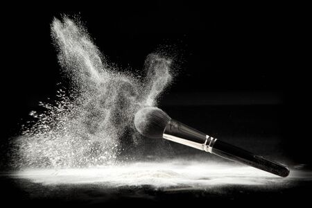 black powder: an image of a cosmetic powder brush, thrown in white loose powder, shot on black backgrownd. Stock Photo