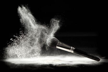 polvos: una imagen de un pincel de cosm�ticos en polvo, iniciada en polvo suelto blanco, filmada en backgrownd negro.