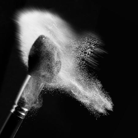 loose skin: a detail of a powder brush, in motion, shaking off white loose powder, shot on black backgrownd. Stock Photo