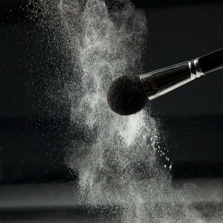 a detail of a powder brush, shaking off white loose powder, shot on black backgrownd. photo