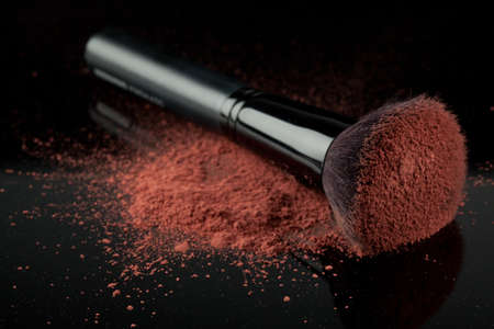 flat brush: a flat blush brush with pink blush on it, placed on some loose powder blush, shot on black backgrownd.