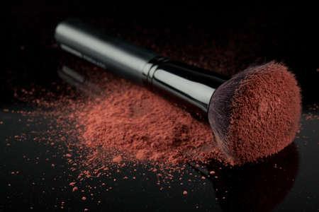 loose skin: a flat blush brush with pink blush on it, placed on some loose powder blush, shot on black backgrownd.