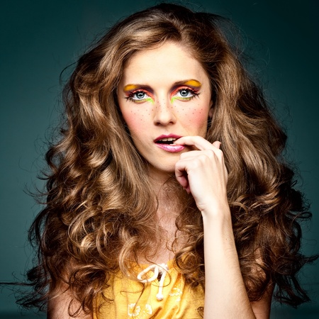 a studio portrait of a young woman with long, blonde and wavy hair and blue eyes. her make-up is very colorful; it is inspired by the 60s style and she has freckles drawn on her cheeks. she has one hand up to her face and one finger in her mouth, which g