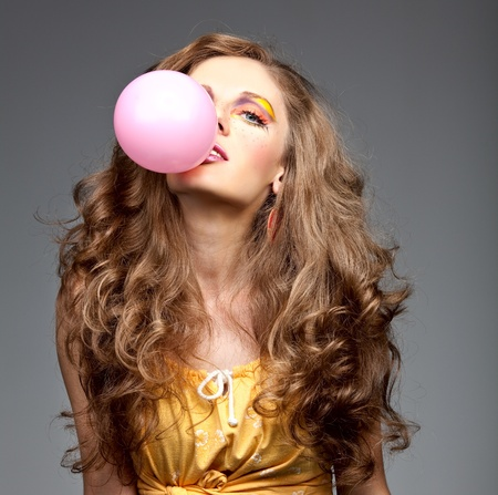 a studio portrait of a young woman with long, blonde and wavy hair and blue eyes. her make-up is very colorful; it is inspired by the 60s style and she has freckles drawn on her cheeks. she is posing with her head backwards and she has a big pink bubbleg photo