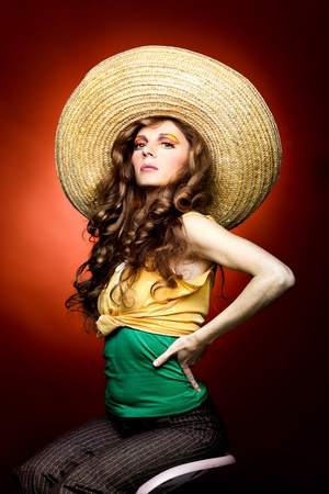 a studio portrait of a young woman with long, blonde and wavy hair and blue eyes. her make-up is very colorful; it is inspired by the 60s style and she has freckles drawn on her cheeks. she is posing sitting on a chair, with a big sombrero on her head an photo