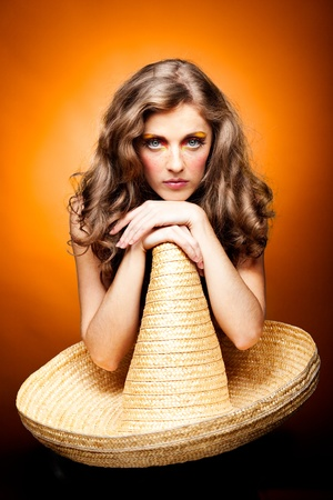 a studio portrait of a young woman with long, blonde and wavy hair and blue eyes. her make-up is very colorful; it is inspired by the '60s style and she has freckles drawn on her cheeks. she is posing sitting on a chair, leaning with both hands on the top Stock Photo - 8259380