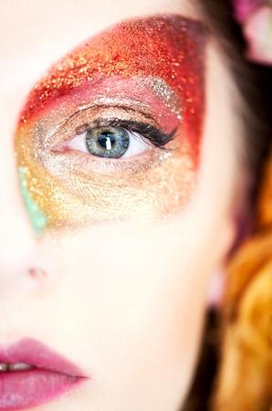 glitter makeup: un retrato de estudio de la mitad de una cara de una mujer joven con cabello rubio y ojos azules, disponer en su espalda entre hojas amarillas, vistiendo un oto�o color maquillaje. Ella tiene una hoja estilizada dibujada con glitter en uno de sus ojos.  Foto de archivo