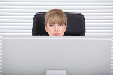 Businesswoman in her office looking over the monitor Stock Photo - 8259343