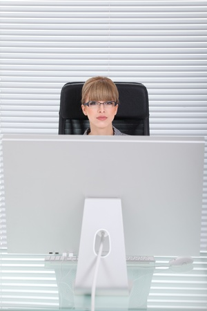 Young business woman behind her monitor photo