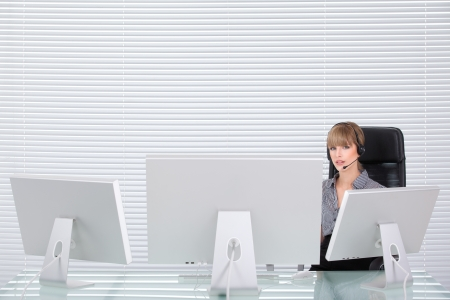 Secretary with headphone and multiple monitors in her clean office Stock Photo - 8259354