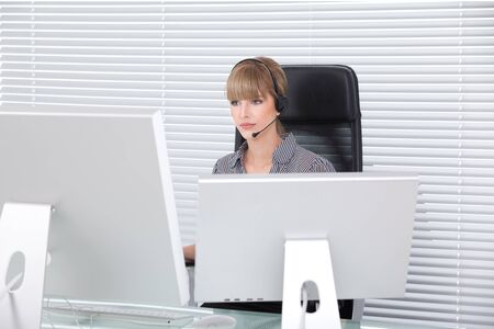 Secretary with headphone and multiple monitors in her clean office Stock Photo - 8259349