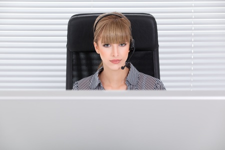 Portrait of a young secretary  in her clean office with headphones Stock Photo - 8259355