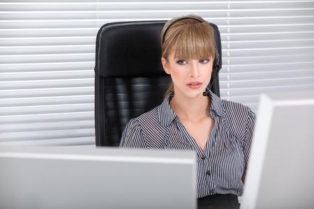 Secretary with headphone and multiple monitors talking Stock Photo - 8259370