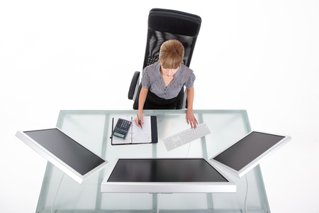 Bird eye view of a businesswoman in her office looking on her monitors Stock Photo - 8259334