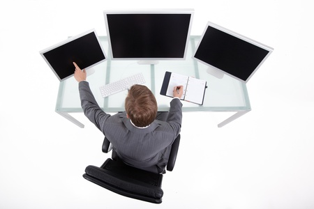 Businessman in his clean high tech office looking on the monitors upper view Stock Photo - 8259332