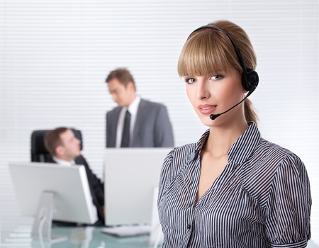 secretary with headphone and her colleagues in the background