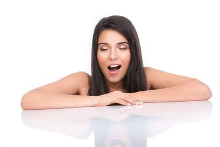 a portrait of a young woman, posing on a white background. she has her arms on a white table and a bored face expression. she is yawning.  photo