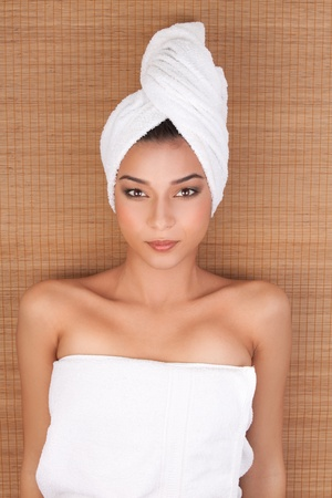 a portrait of a young woman at a day spa, layed on her back, on a mat, with her hair and body wrapped in white towels. photo