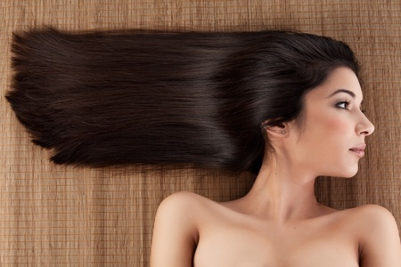 a close-up profile portrait of a young woman, laying on a spa mat. her hair is laying strait, in a horizontal direction. photo