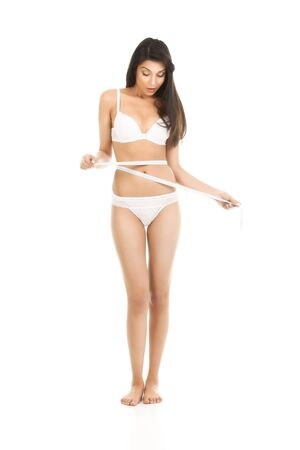 tanned body: a studio shot of a young, beautiful woman, measuring her waist line. she is dressed in her underwear, she is looking down and she seems surprised.