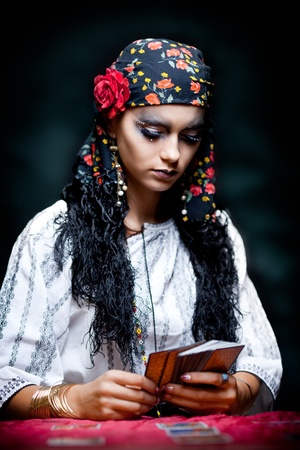 a portrait of a gypsy fortune teller, sitting at a table and looking at the tarot cards that she holds in her hands. photo