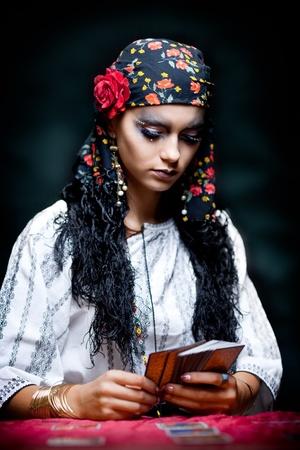 gitana: un retrato de una pitonisa de gitana, sentado en una mesa y mirando las cartas del tarot que tiene en sus manos.
