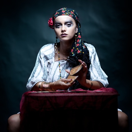 a portrait of a gypsy fortune teller, sitting at a table and mixing the tarot cards that she holds in her hands. she is looking at the camera. photo