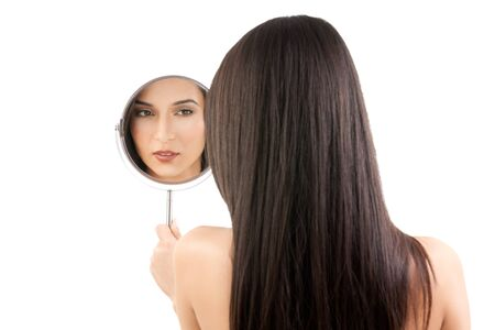 a beauty studio picture of a young woman looking in a mirror, while her back is turned to the camera. the mirror held over her left shoulder reflects her face. photo