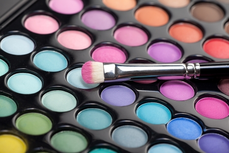 a close-up image of a eye-shadow set, with a professional makeup brush with pink pigment on it