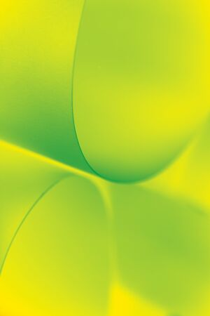an abstract macro photo of curve shapes made up of paper, coloured in yellow and green Stock Photo - 8991374