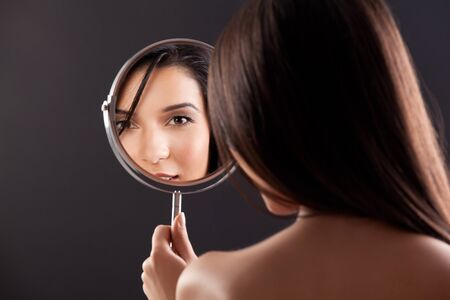 a beauty studio picture of a young woman looking in a mirror, while her back is turned to the camera. the mirror held over her left shoulder reflects her smiling face. photo
