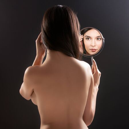 a beauty studio picture of a young woman looking in a mirror, while her back is turned to the camera. the mirror held over her left shoulder reflects her smiling face. Stock Photo - 8991354