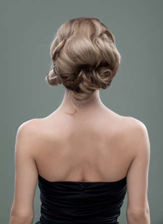 a head and shoulders image of a young woman, from the back. her hair is long and blonde and she is showing an interesting, wavy hairstyle. Stock Photo - 9169840