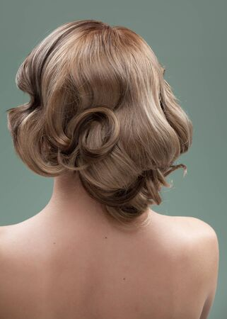 a head and shoulders image of a young woman, from the back. her hair is long and blonde and she is showing an interesting, wavy hairstyle. photo