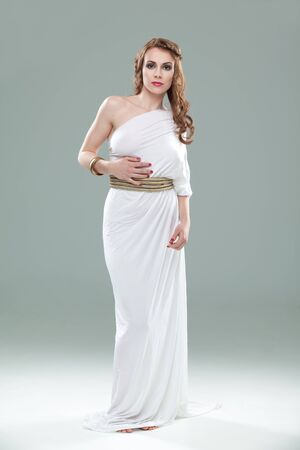a studio portrait of a beautiful young woman, wearing a long, white, ancient greek inspired dress, smiling. photo