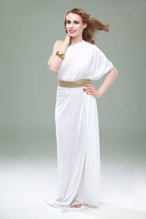 a studio portrait of a beautiful young woman, wearing a long, white, ancient greek inspired dress, smiling, with wind blowing in her hair. Stock Photo - 9169782