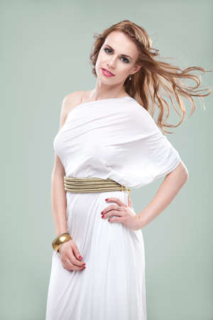 a studio portrait of a beautiful young woman, wearing a long, white, ancient greek inspired dress, smiling, with wind blowing in her hair. photo
