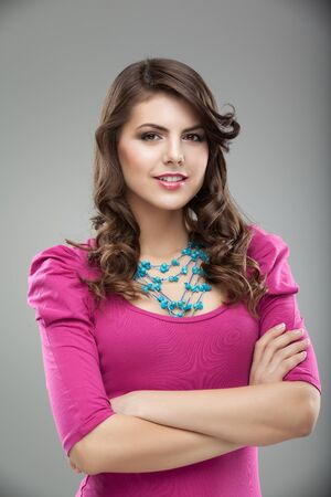 a studio portrait of a young, pretty woman, in colorful clothes and accessories, smiling, with her hands around her body photo