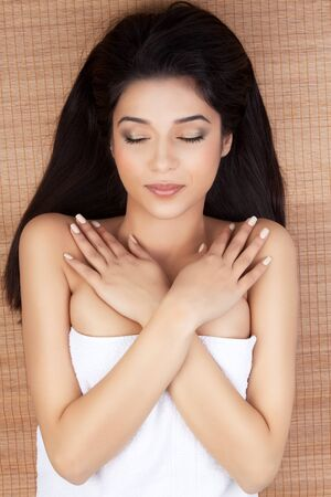portrait of a beautiful, young woman, at a spa, lying on her back on a bamboo mat, smiling, with her hands on her shoulders and her eyes closed photo