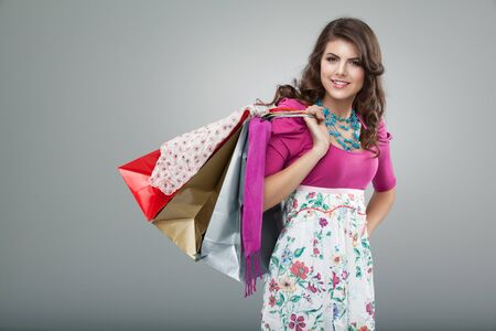 purchases: studio portrait of a young woman in a colourful outfit, holding in one hand three shopping bags. she is laughing and looking very happy. Stock Photo