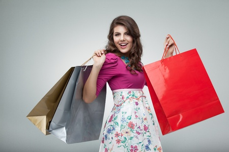 happy shopper: studio portrait of a beautiful young woman, in a colourful outfit, holding in her hands a few shopping bags. she is laughing and looking very happy. Stock Photo